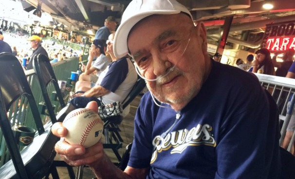 Hospice patient Russell holds the game ball he received from the Milwaukee Brewers