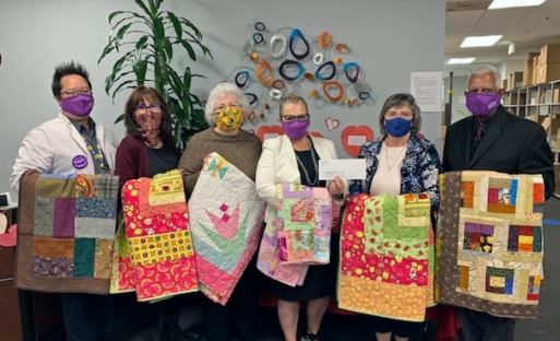 Six Guild members hold up quilts they have created