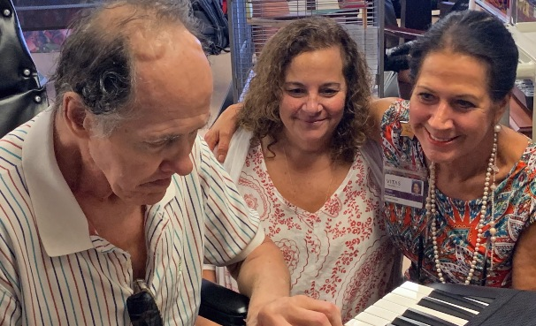 Patient David Laessig plays for music therapy intern Monica Bonasso and Volunteer Services Manager Gayle Stevens